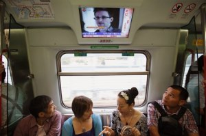 File photo of passengers watching a TV screen broadcasting news of Snowden on a train in Hong Kong